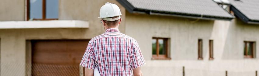 Uomo con progetti sottobraccio davanti ad una casa