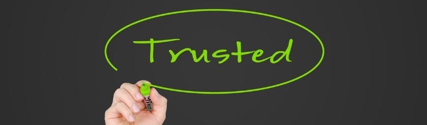"""Scritta cerchiata """"trusted"""" in verde su sfondo grigio scuro con pennarello verde e mano in vista"""