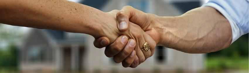 Stretta di mano tra uomo e donna con anello di fronte ad una casa che si vede sfocata sullo sfondo