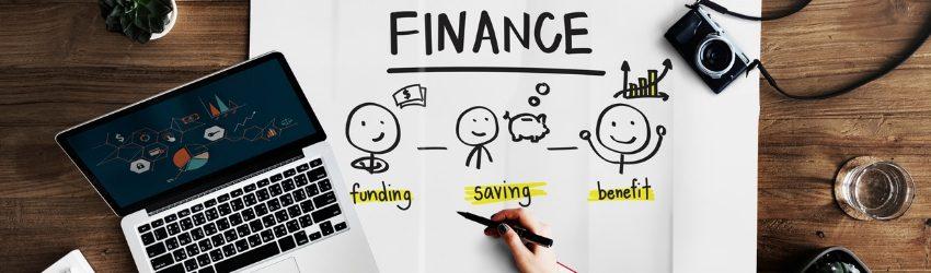 bilancio 2019 fondi stanziati: mano che disegna su un foglio bianco schema di finanza con tre omini stilizzati su una scrivania con sopra computer, tazza e macchina fotografica