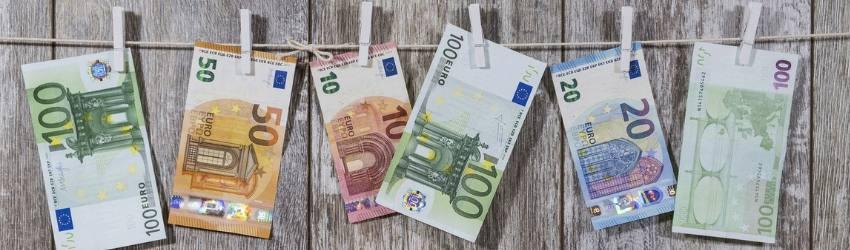 bilancio 2019 fondi stanziati: banconote euro di diverso valore appesi ad un filo con mollette bianche su sfondo di parete in legno
