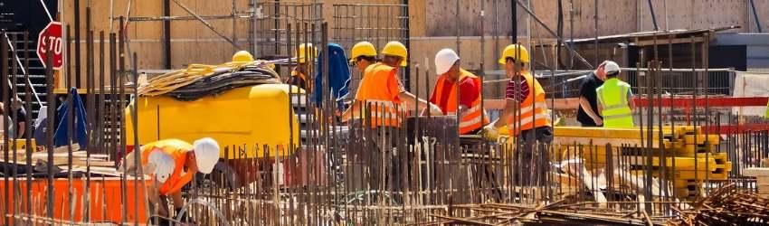 operai con casco giallo e gilet arancione al lavoro in un cantiere edile