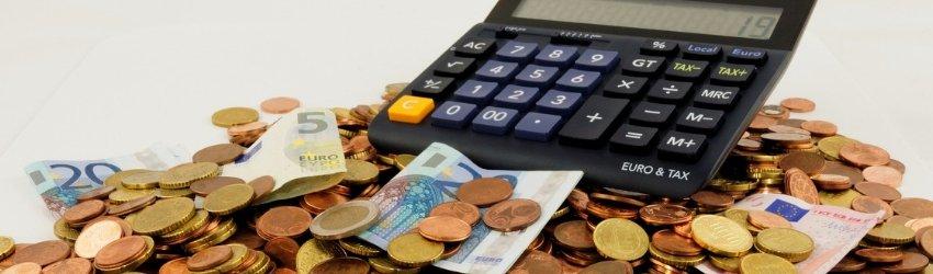 Calcolatrice sopra un mucchio di euro in monete e banconote su tavolo bianco