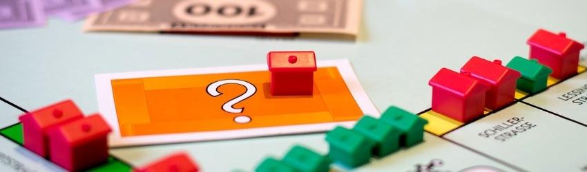 Gioco Monopoli con casette colorate, foglietto con punto di domande e soldi finti