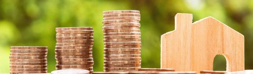 tre pile di monete con altezza crescente accanto ad una statuina di casa in legno