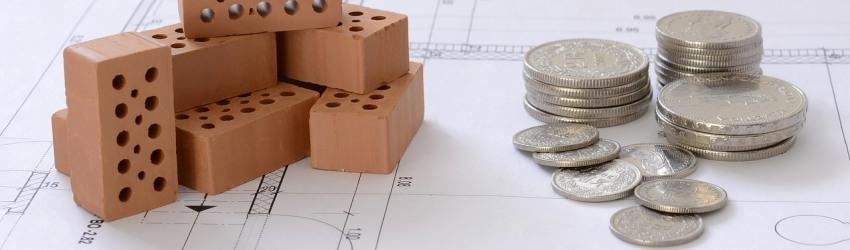 Mattoni e monete sopra progetto architettonico