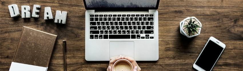 """donna seduta ad un tavolo con tazza piena fra le mani di fronte a un computer, una piantina grassa, uno smartphone, un'agenda con una penna e la scritta """"dream"""""""