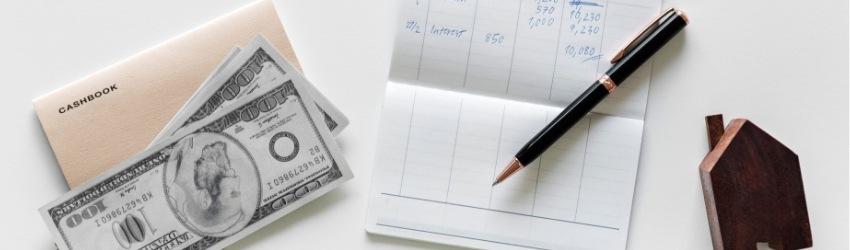 tavolo bianco su cui sono poggiate banconote, un libretto degli assegni con una penna e una miniatura in legno scuro di una casetta