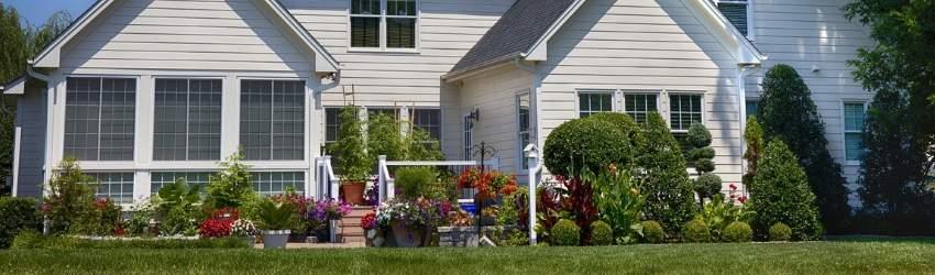 Bonus Verde: giardino curato con piante, fiori, prato tagliato, mobilio da giardino. con casa bianca di legno sullo sfondo