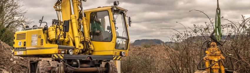 permesso costruzione suolo pubblico: escavatore guidato da un uomo che sta lavorando in un terreno agricolo
