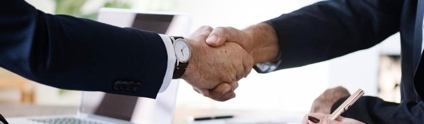 Elemento Chiave della Vendita: uomini d'affari che si stringono la mano al di sopra di una scrivania ingombra per la Vendita avvenuta
