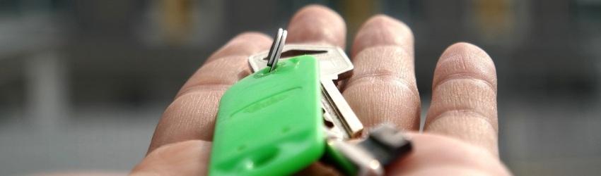 Elemento chiave della Vendita: mano di uomo tesa che regge un mazzo di chiavi con un portachiavi verde su sfondo di case sfocate