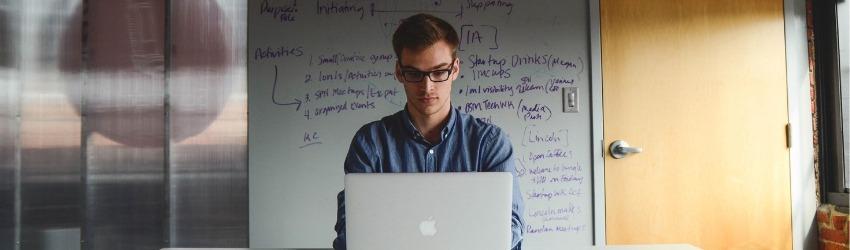 Regime Forfettario 2019: ragazzo che scrive al pc davanti ad un muro con schemi aziendali scritti sopra dentro un ufficio