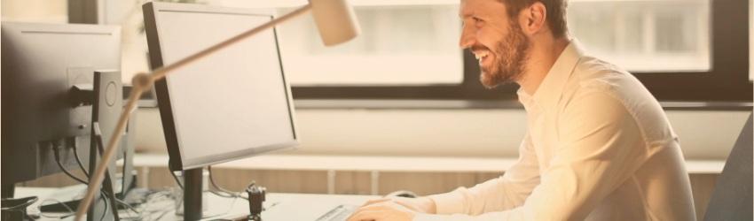 Uomo sorridente seduto ad una scrivania mentre lavora ad un computer dentro una stanza di ufficio. Sullo sfondo una finestra