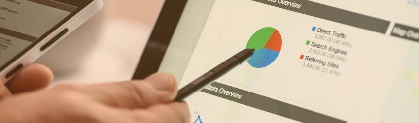 Mano di uomo che con un pennino indica uno schermo di computer su cui compare un grafico a torta e diversi dati relativi al traffico di visitatori su un sito web