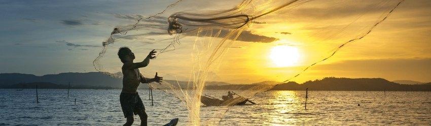 affrontare vendite impossibili: pescatore su una barchetta di legno che getta la sua rete in mare al tramonto