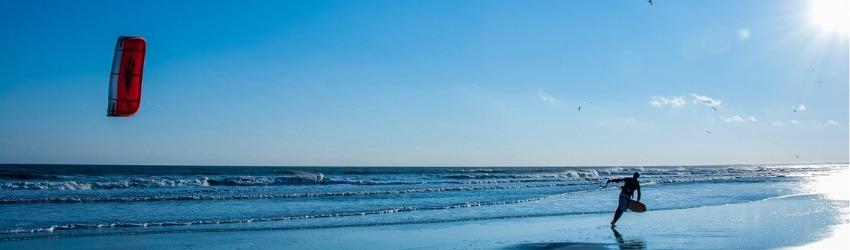affrontare vendite impossibili: uomo che corre sulla spiaggia tenendo il filo di un aquilone