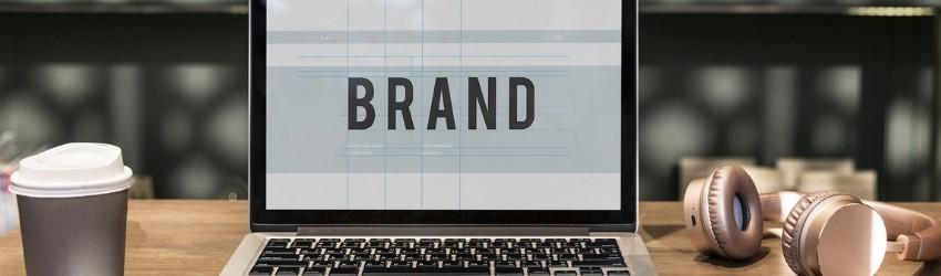 """promuovere impresa edile: pc poggiato su un tavolo di legno di fianco ad una tazza che mostra sullo schermo la parola """"brand"""""""
