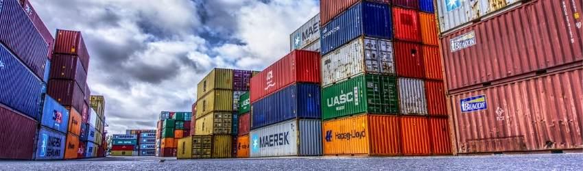 Permesso di costruzione casi: serie di container corolati sovrapposti, poggiati sull'asfalto con sfondo di cielo con nuvole