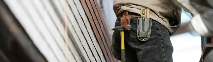 Circolare Applicativa NTC 2018: operaio con strumenti di lavoro attaccati alla cintura che lavora