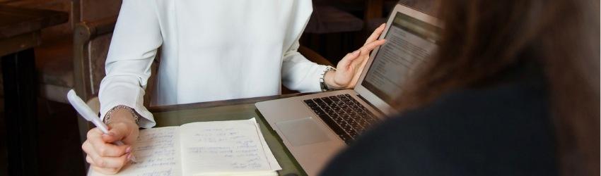Vendi di più imparando ad auto-valutarti: venditrice seduta a un tavol con dei documenti davanti che conversando con una cliente le mostra qualcosa sullo schermo di un computer