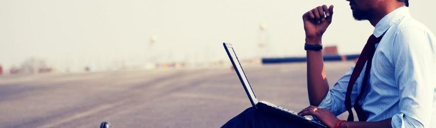 17 ipotesi edilizia: uomo d'affari seduto sull'asfalto con un computer poggiato sulle gambe che pensa