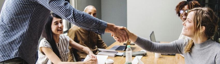 Gestire relazione Open&Go Build: stretta di mano tra imprenditore edile e committente ad un tavolo con altri collaboratori che osservano
