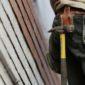 vendere più materiali edili: lavoratore con cintura da lavoro con martello e taglierino che sta lavorando in un cantiere